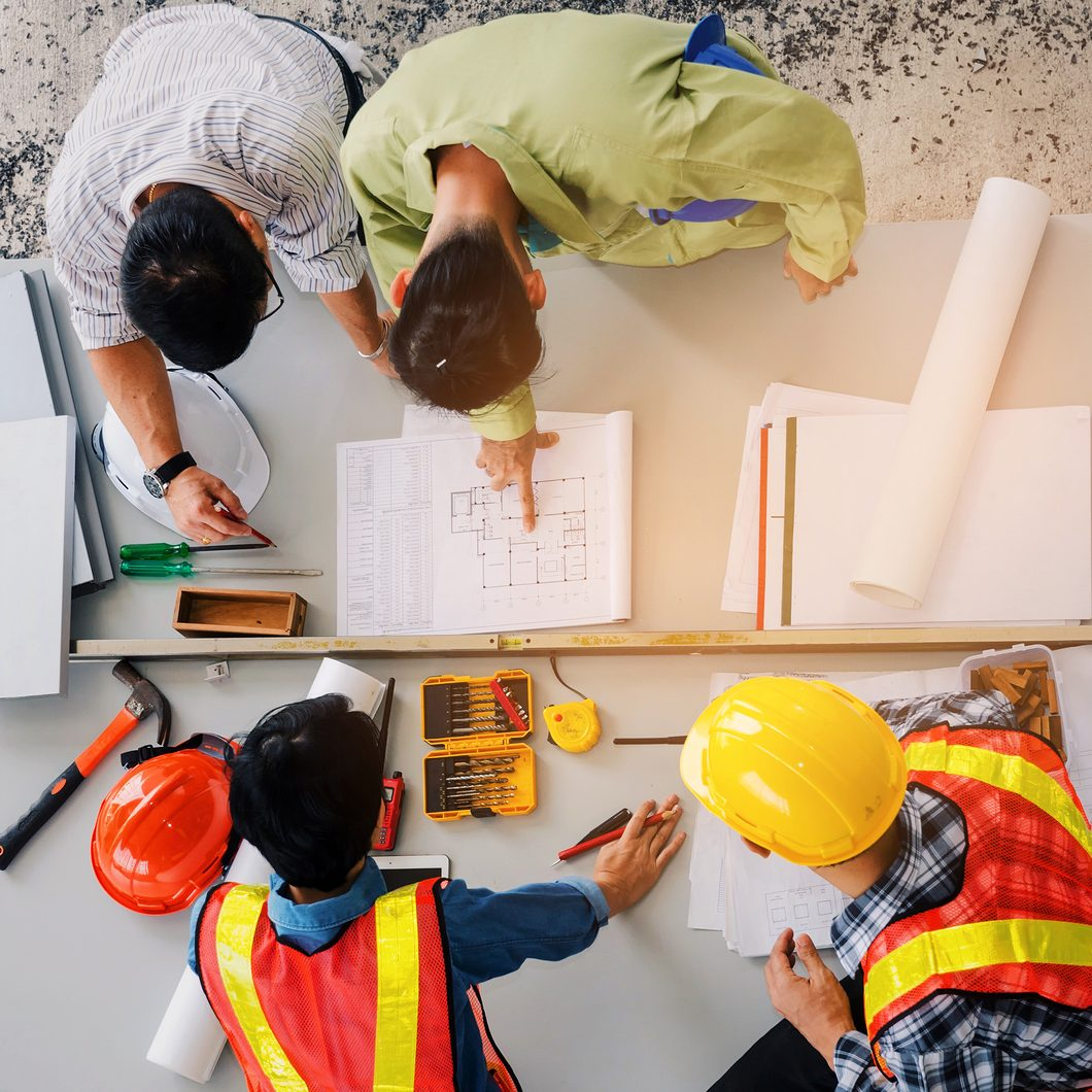 top view of group of engineer, technician and architect planning about building plan with blueprint and construction tools on the conference table at construction site, business and industry concept